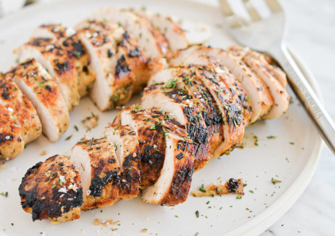 side view of two sliced turkey breast tenderloins sitting on a white plate