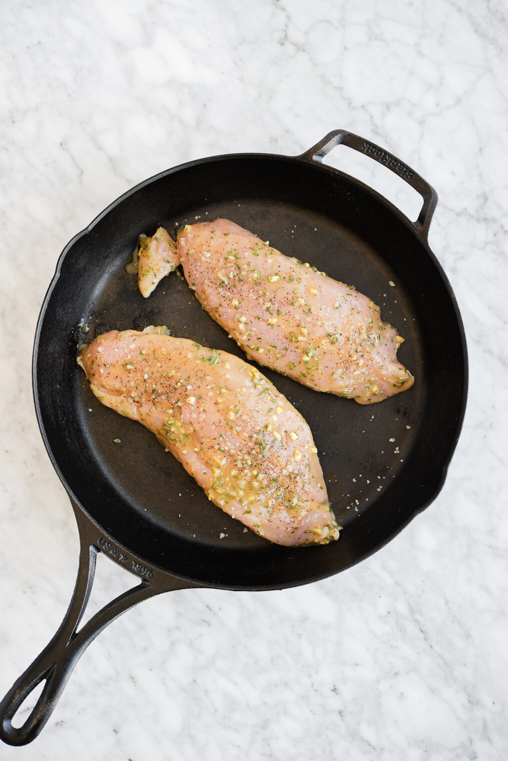 top view of two marinaded turkey breast tenderloins searing in a cast iron skillet
