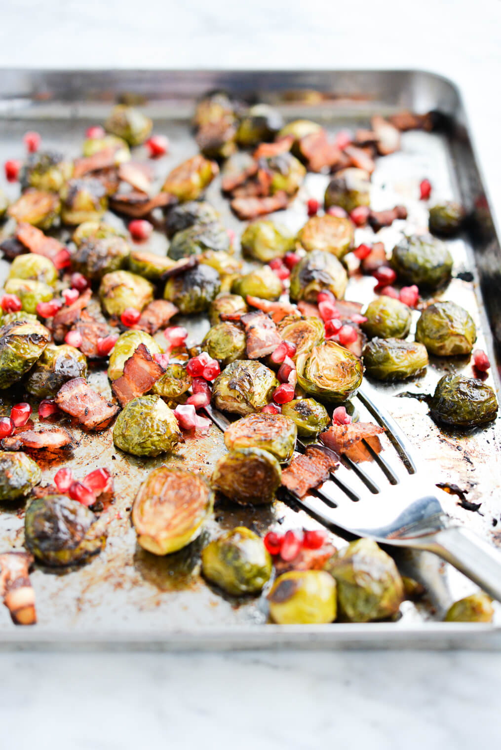 side view of roasted brussels sprouts, pomegranate seeds, and bacon on a sheet pan