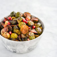 a bowl of roasted brussels sprouts, pomegranate seeds, and bacon in a marble bowl on a marble surface