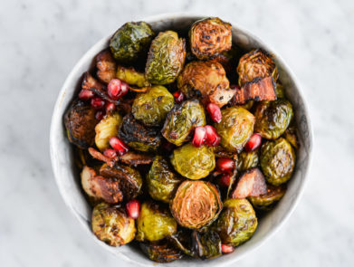 top view of a bowl of roasted brussels sprouts, pomegranate seeds, and bacon in a marble bowl on a marble surface