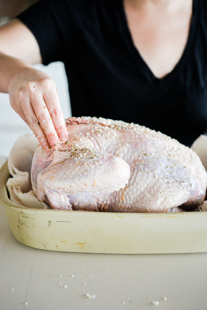 a raw whole turkey being rubbed with butter and herbs