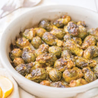 whole roasted brussels sprouts in a round, white ceramic dish on top of a linen towel