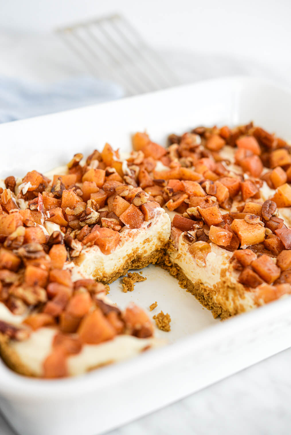 side view of a dish of apple pie cheesecake bars with one bar missing