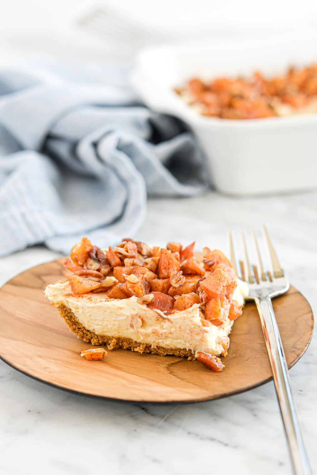 side view of a apple pie cheesecake bar sitting on a wooden plate on a marble surface