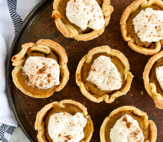 the top view of a plate of mini pumpkin pies topped with homemade whipped cream