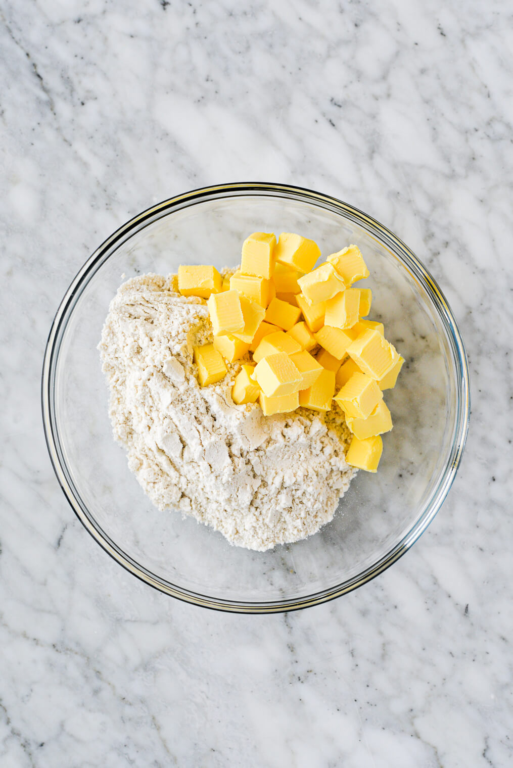 a clear bowl with cubed butter and flour
