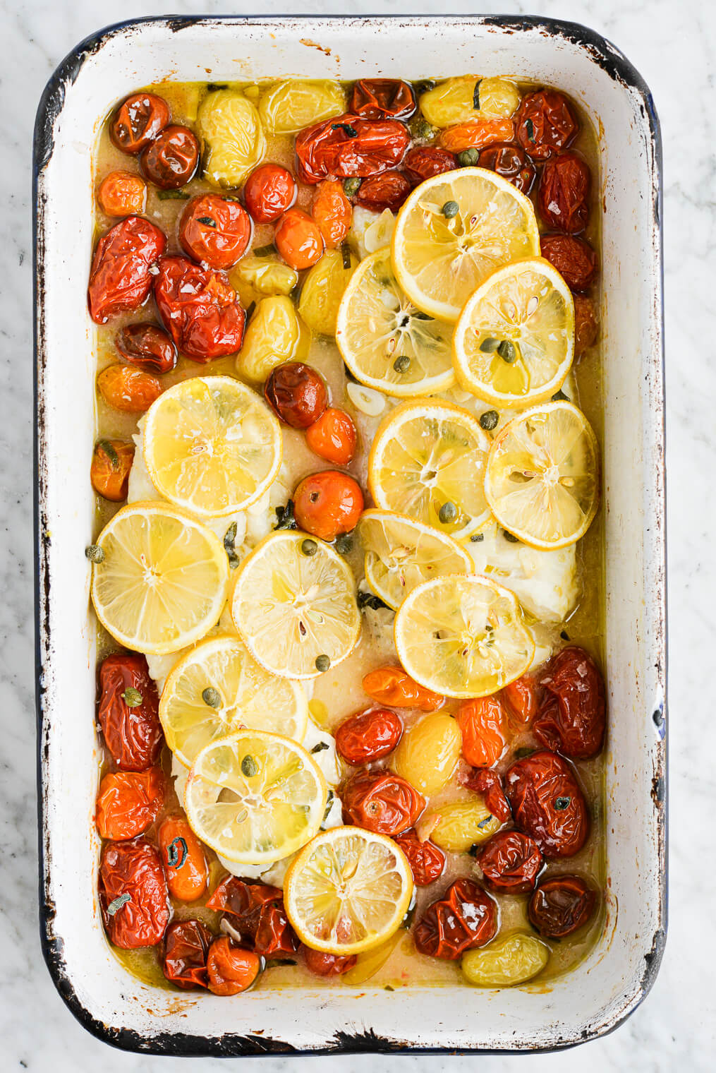 the top view of a roasting dish of baked cod topped with thin sliced lemons and roasted tomatoes
