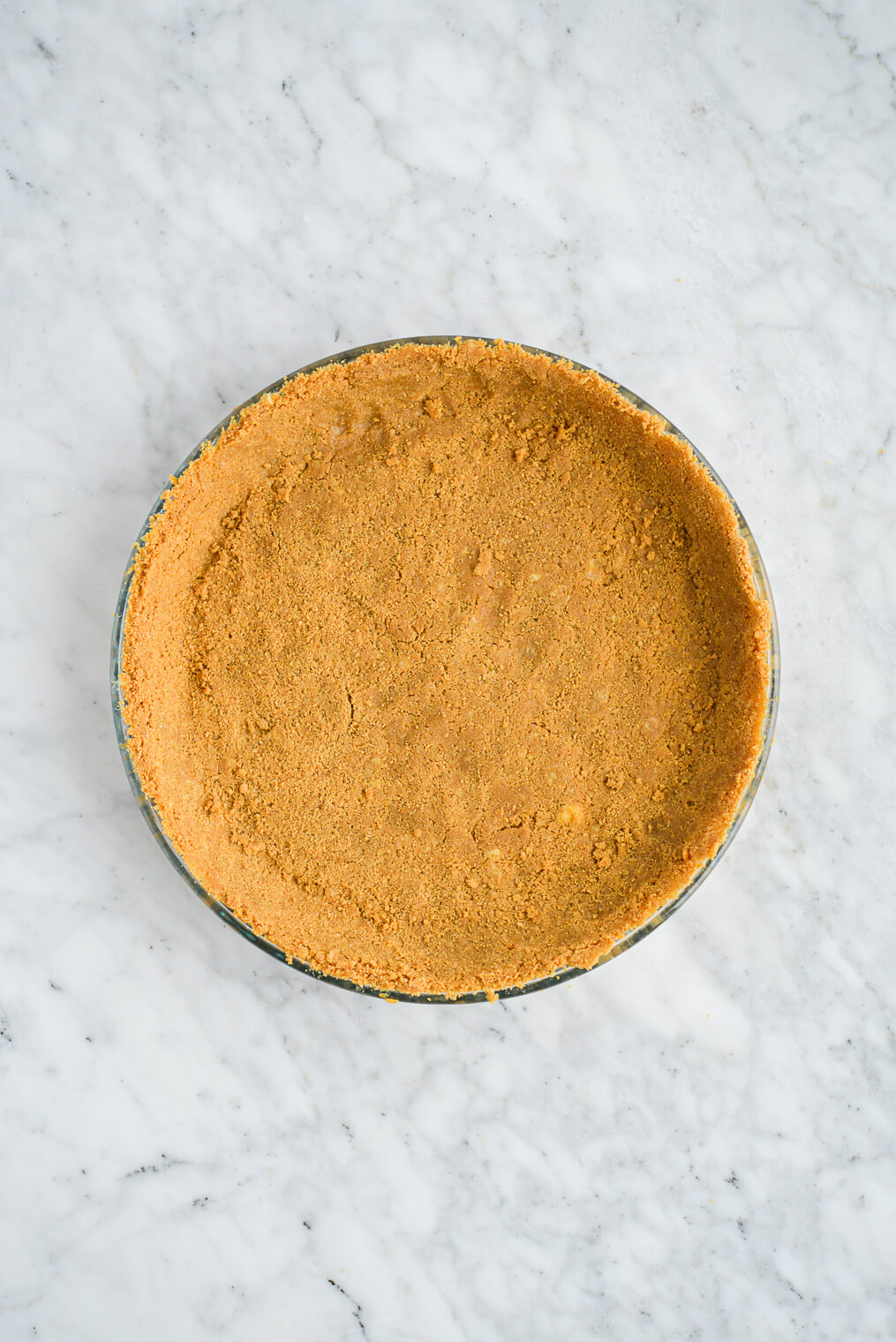 a graham cracker crust pressed into a clear glass pie plate sitting on a marble surface