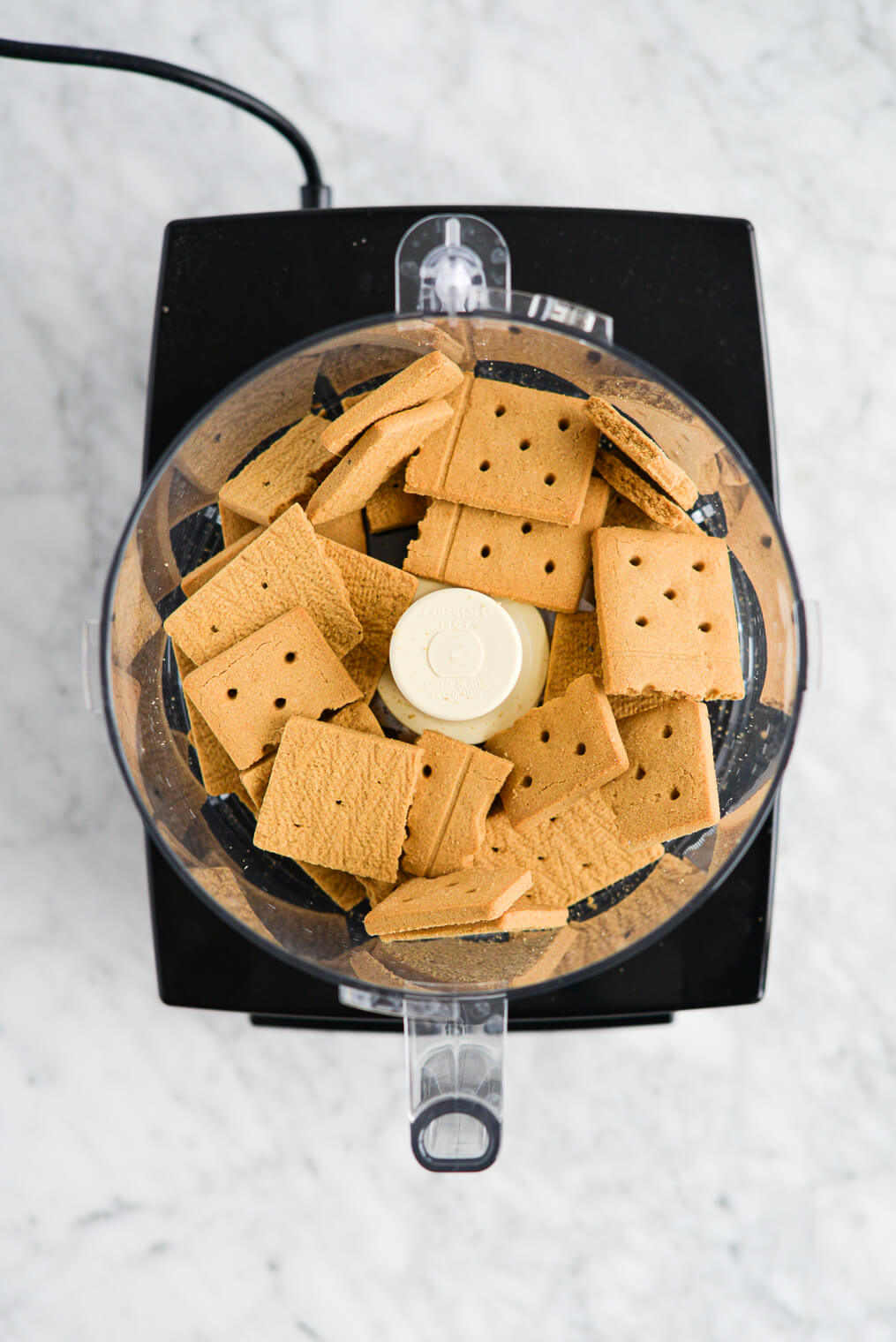 a food processor filled with large pieces of graham cracker