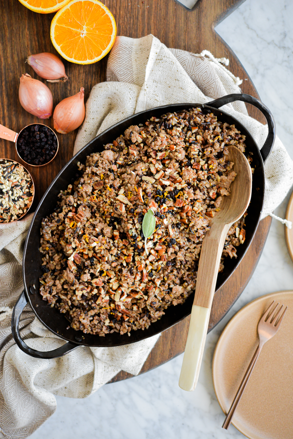 a dish of wild rice stuffing sitting on a wood board next to a halved orange, and whole shallots