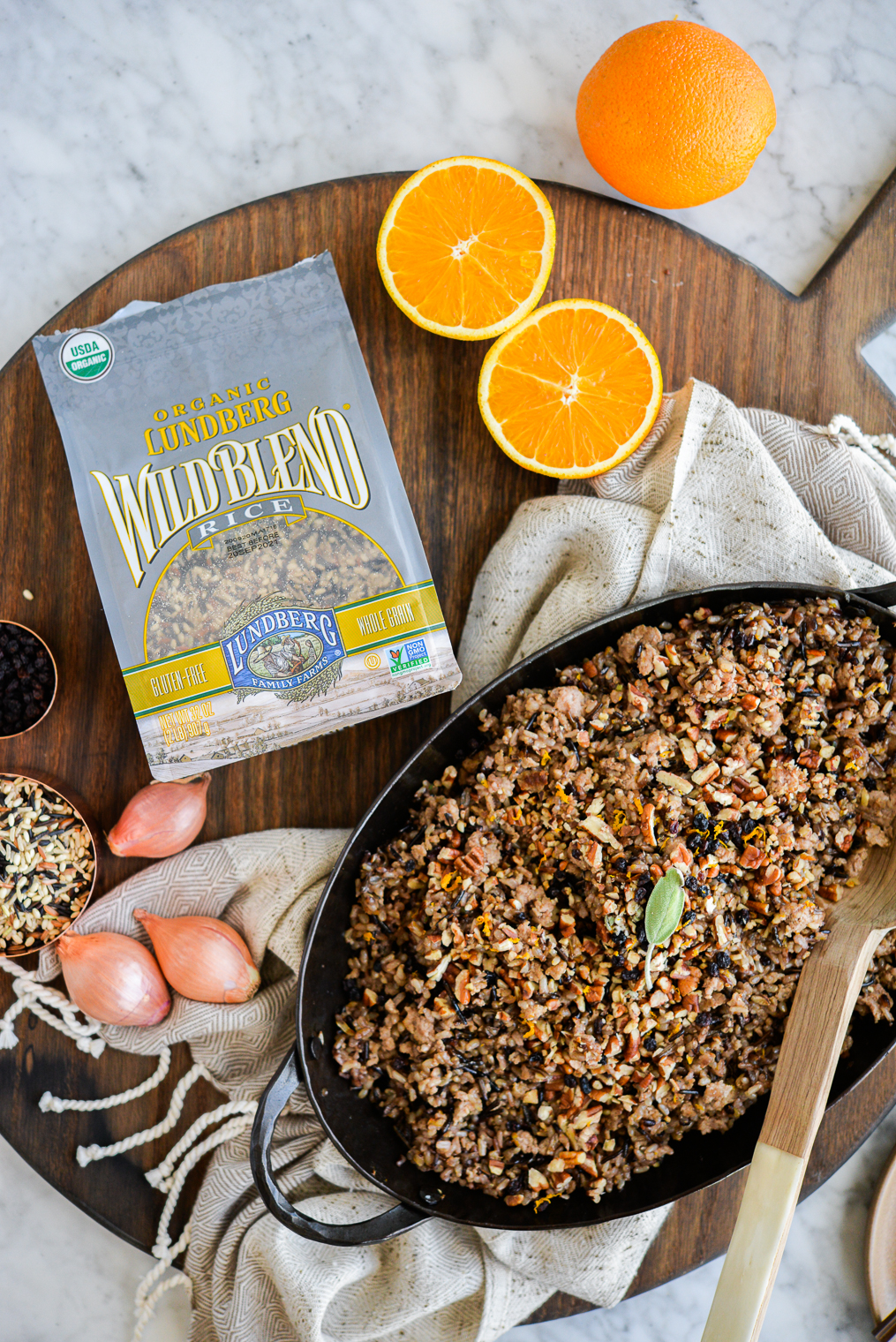 a dish of wild rice stuffing sitting on a wood board next to a bag of Lundberg Wild Rice Blend, a halved orange, and whole shallots