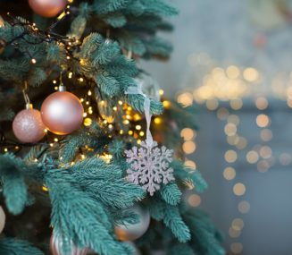 christmas tree with rose gold ornaments against a twinkle light background