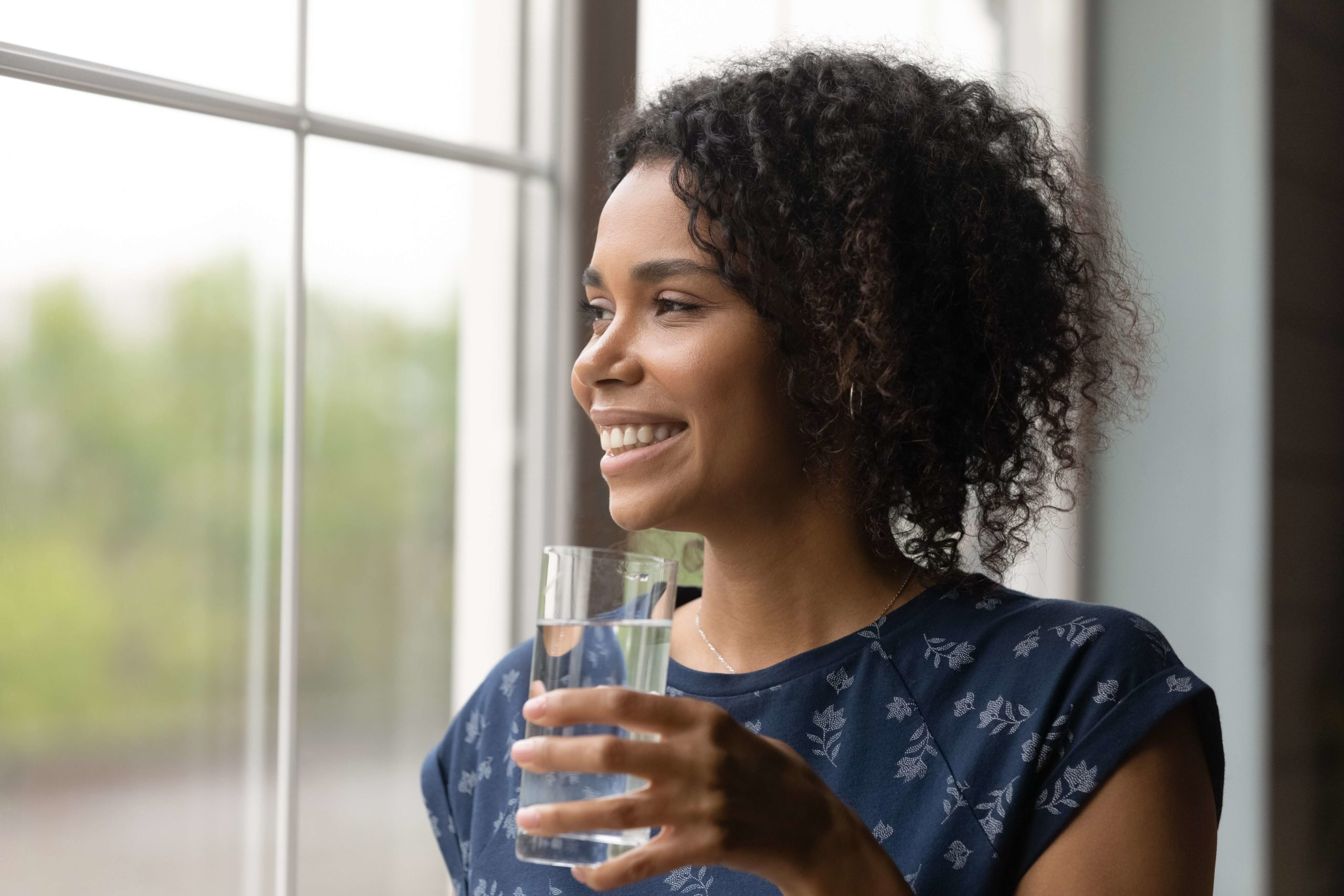 woman drinking water and looking out the window
