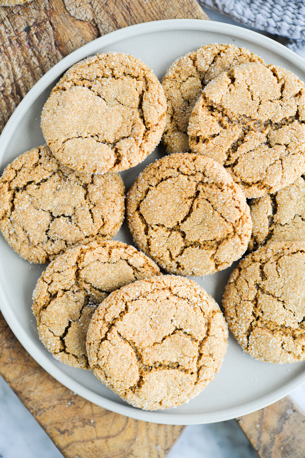 a grey ceramic plate with ginger molasses cookies piled on top of it on a wooden surface