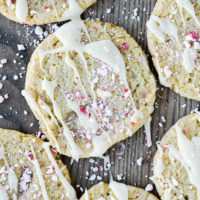 sugar cookies drizzled with white chocolate and crushed peppermints on a wooden surface