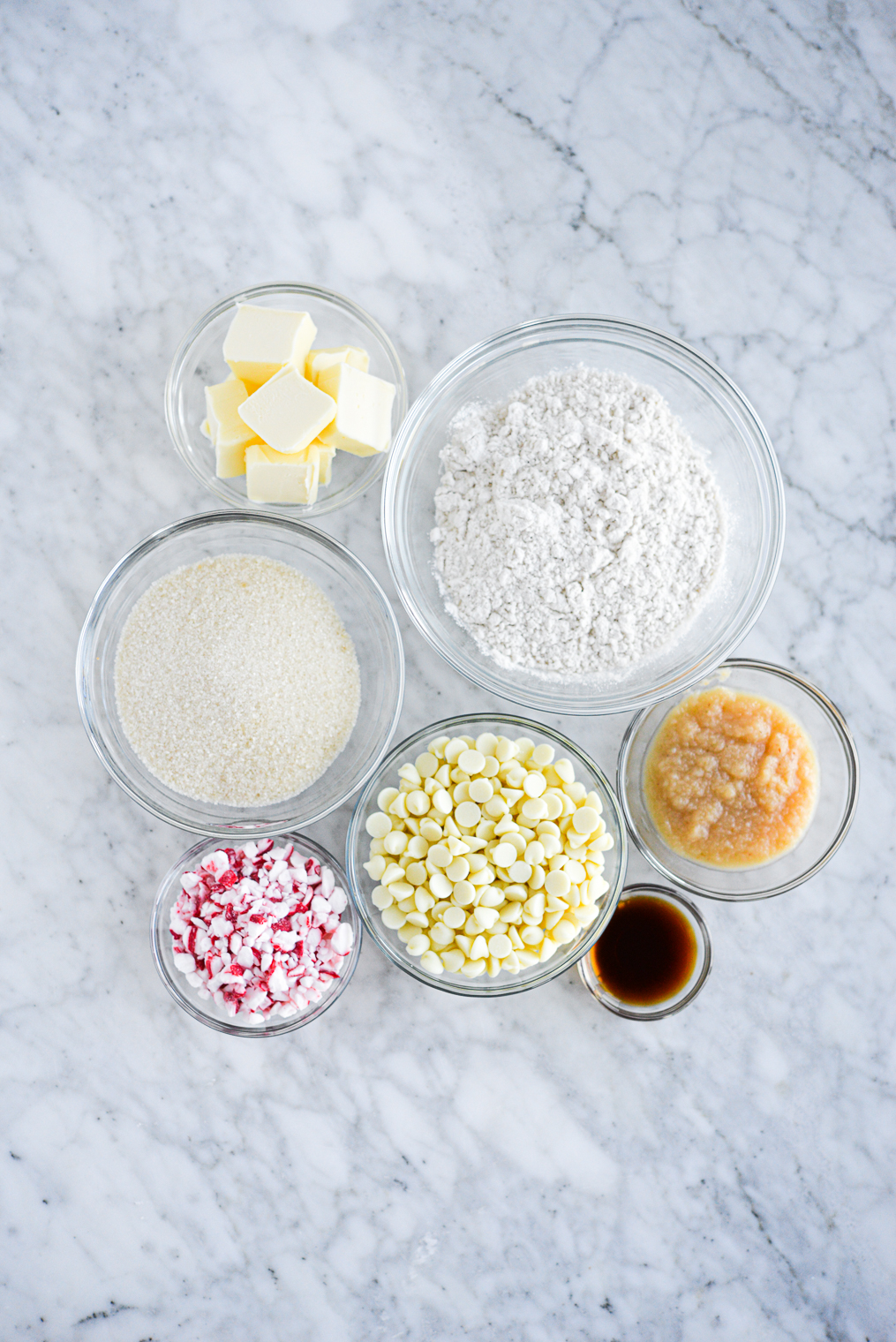 bowls of ingredients for white chocolate peppermint cookies on a marble surface