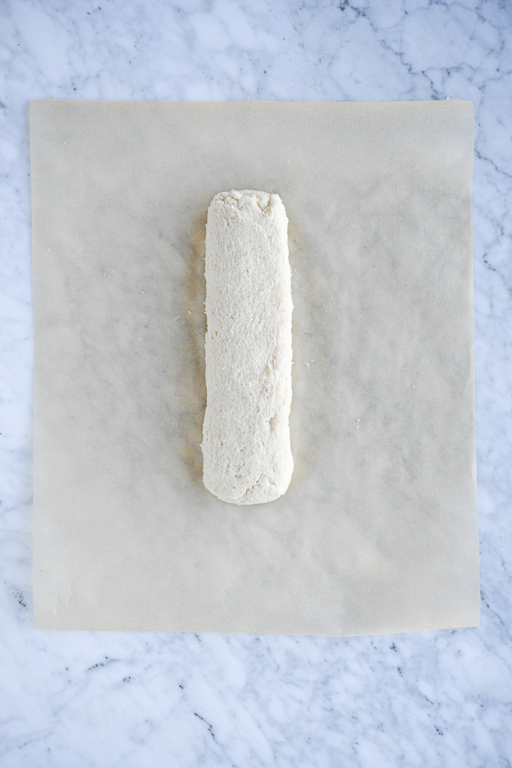 log of sugar cookie dough on brown parchment paper