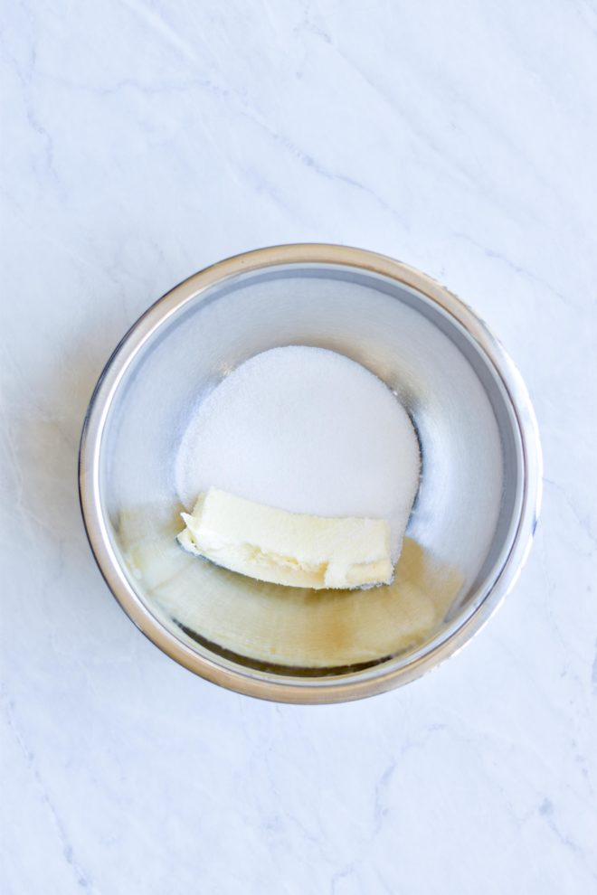 metal bowl on a marble surface filled with a stick of softened butter and sugar