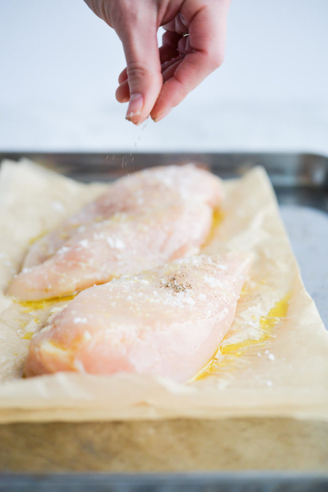 a woman's hand sprinkling ground pepper on raw chicken breasts that are sitting on a parchment paper lined sheet pan and coated in olive oil and sea salt