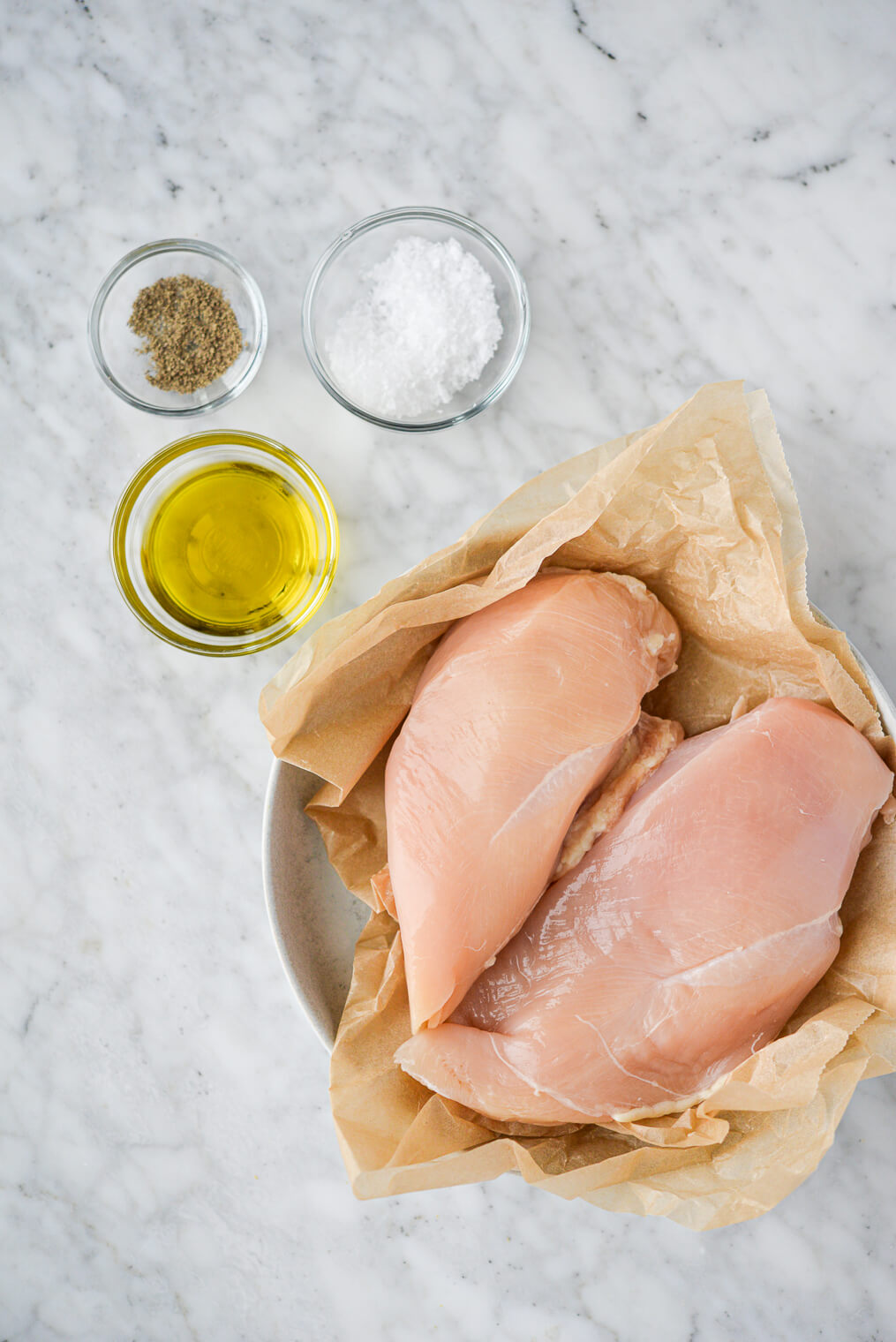 two raw chicken breasts sitting in a parchment paper lined bowl, a small bowl of olive oil, a small bowl of sea salt, and a small bowl of ground pepper sitting on a marble surface