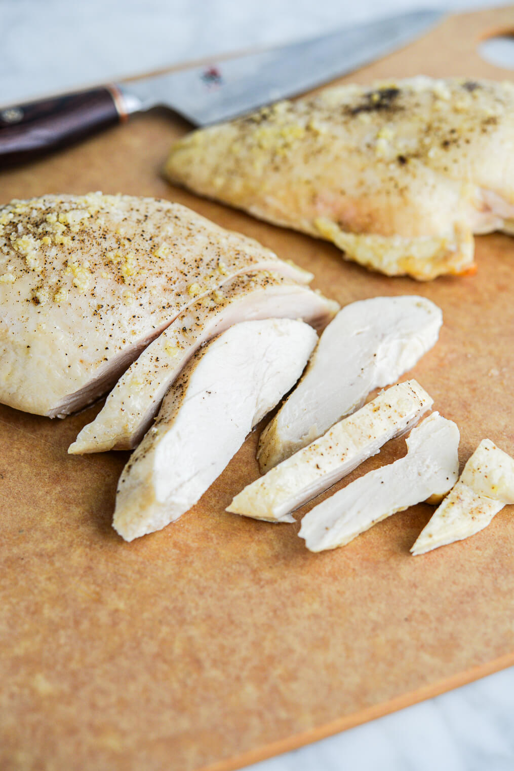 two baked chicken breasts (one sliced and one left whole) sitting on a cutting board next to a knife