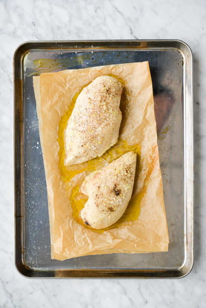 two seasoned and baked chicken breasts sitting on a parchment paper lined baking sheet