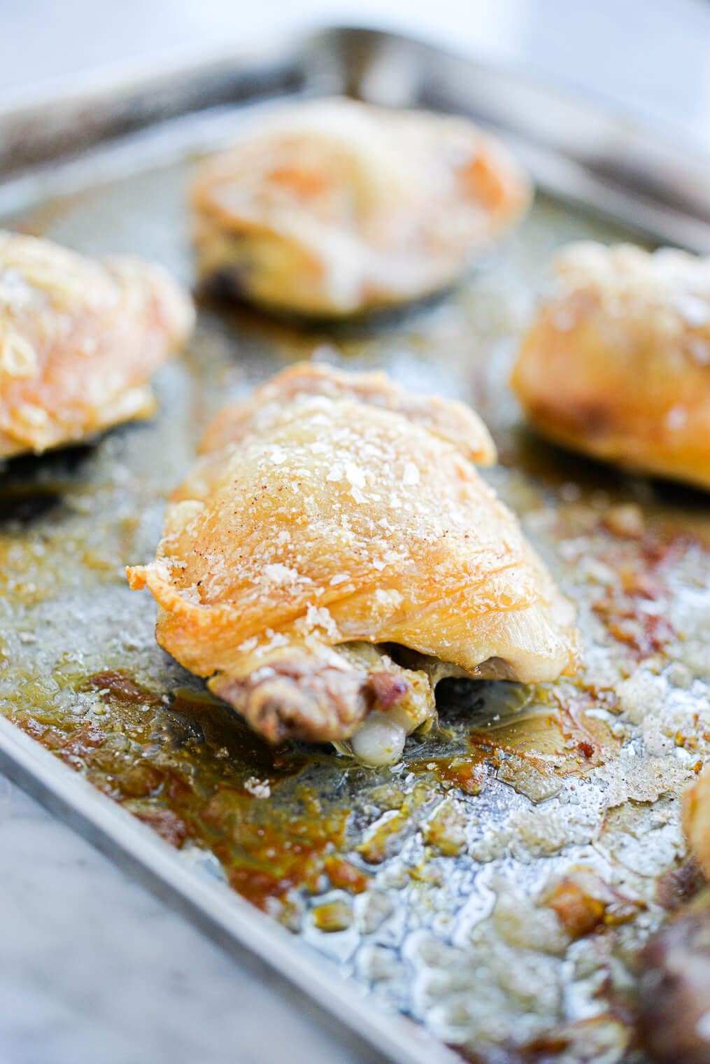 golden brown oven baked crispy chicken thighs on a stainless rimmed sheet pan sitting on a marble surface