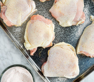 bone-in, skin-on chicken thighs that have been dry brined with sea salt laying on a stainless steel rimmed baking sheet