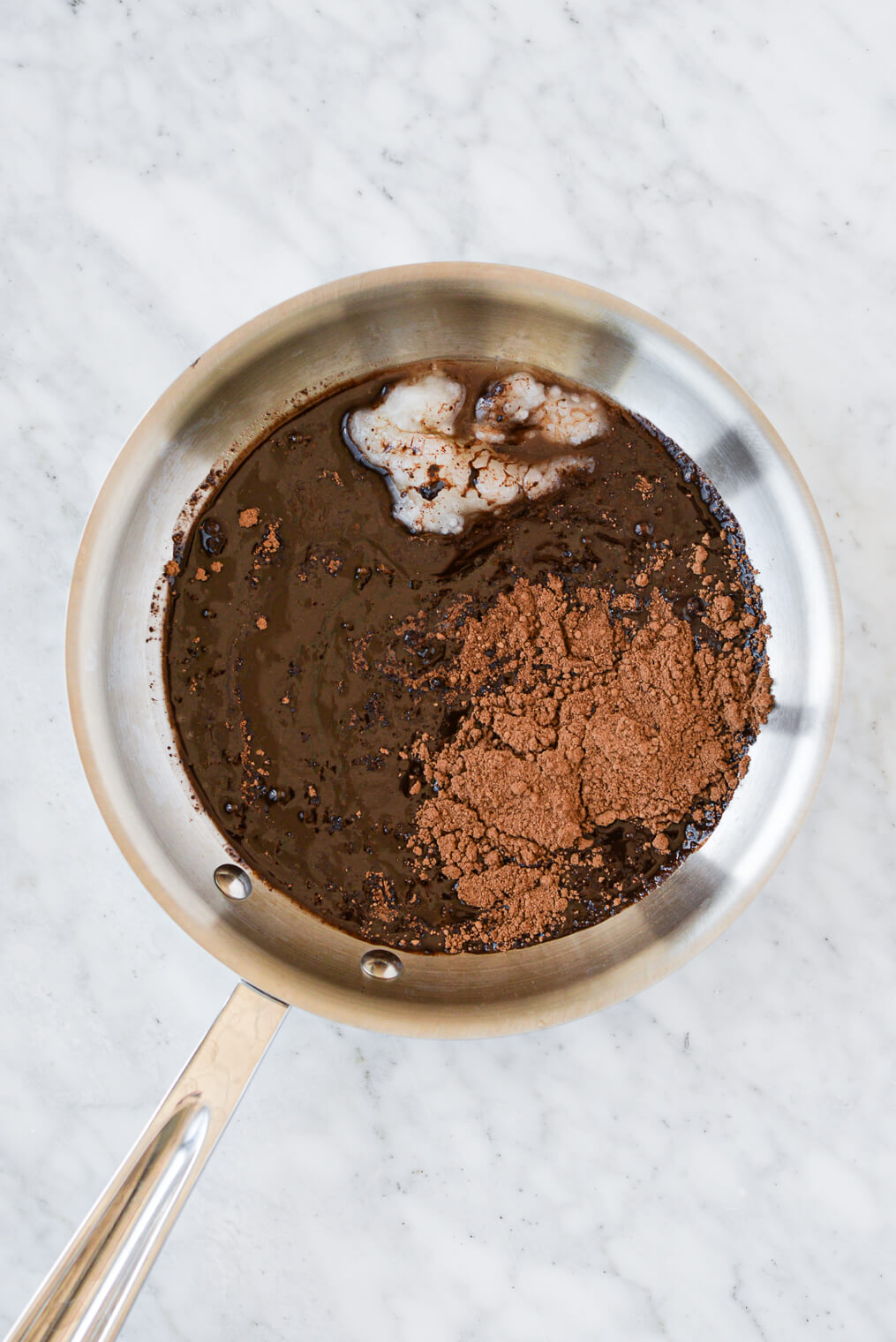 maple syrup, coconut oil, cocoa powder, and vanilla extract unmixed in a stainless steel pot sitting on a marble surface