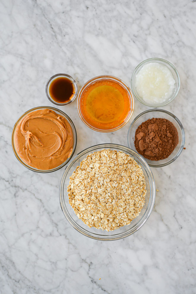 the ingredients for no bake oatmeal cookies (oats, peanut butter, maple syrup, coconut oil, cocoa powder, and vanilla extract) all in separate small glass bowls sitting on a marble surface