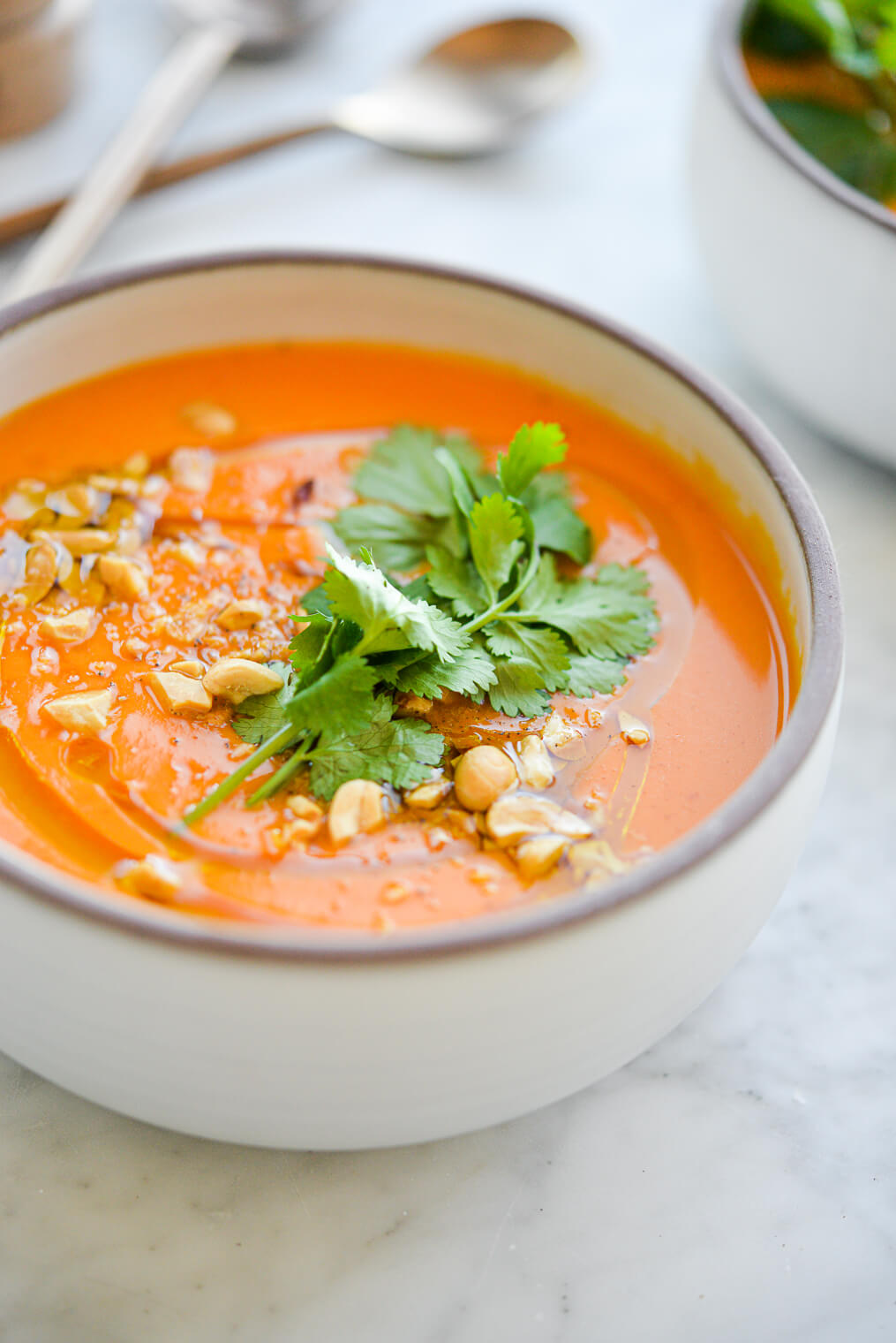 a bowl of bright orange thai carrot soup garnished with fresh cilantro and crushed peanuts sitting on a marble surface