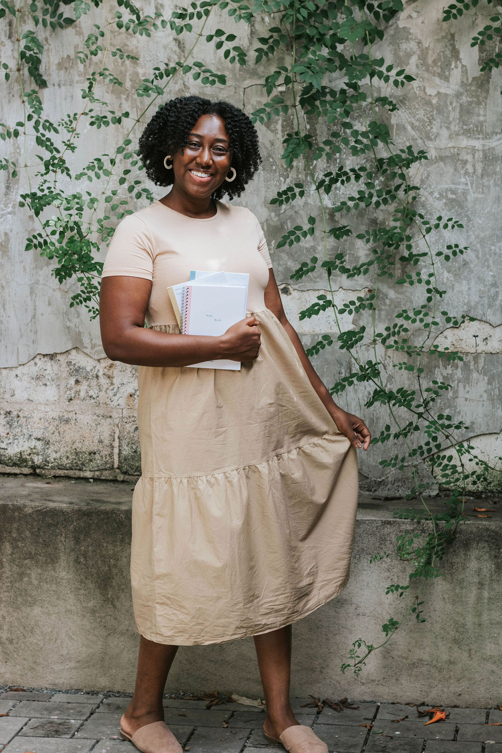 Ashley Brown of Routine & Things standing in front of a wall with greenery growing on it holding notebooks in her hand
