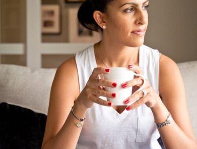 Riyana Rupani of Healthyish and Happy holding a coffee cup sitting on a couch looking off to the side