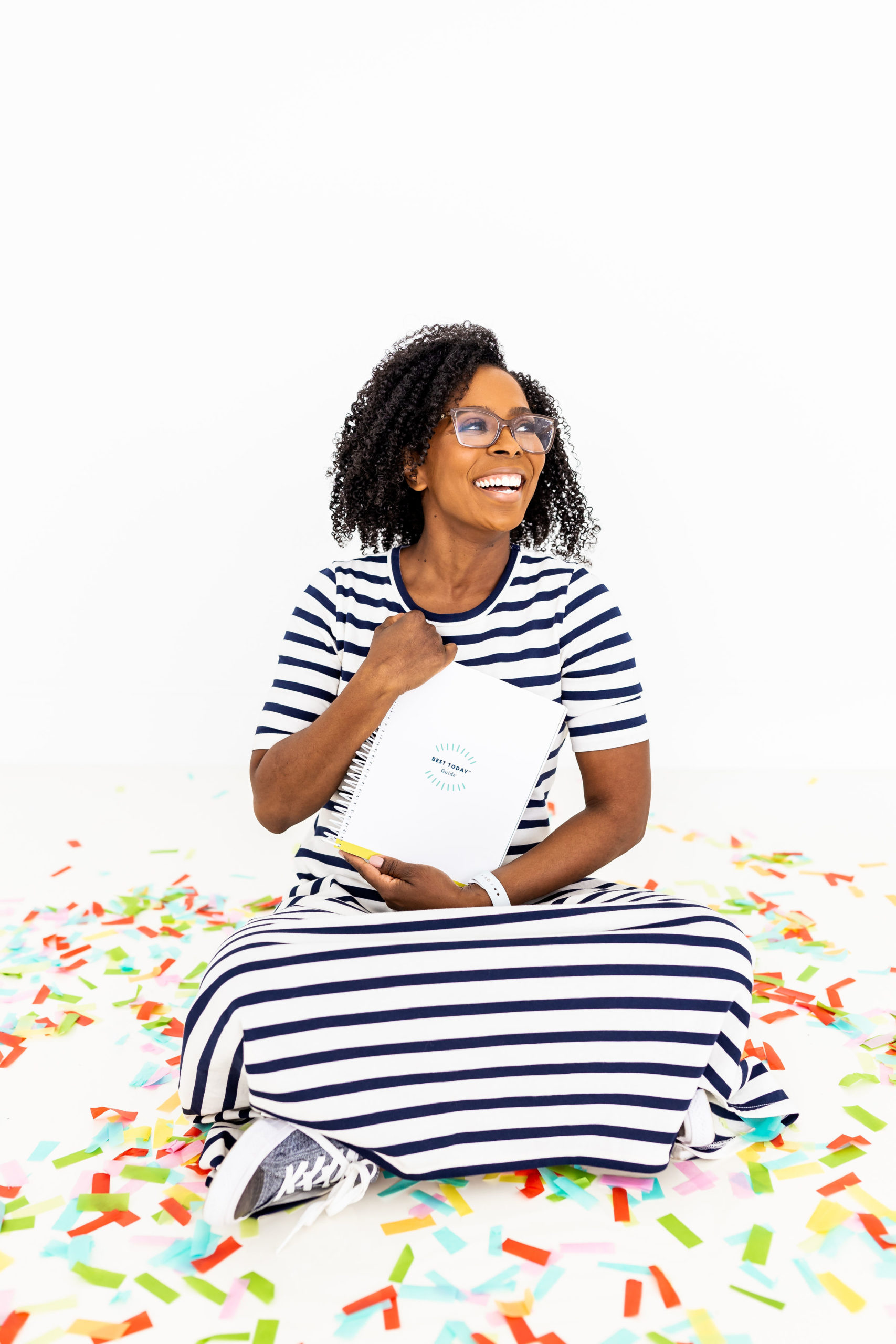 Shunta Grant of The Best Today Brand holding the Best Today Guide while sitting on a confetti covered floor