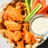 a bowl filled with Instant Pot buffalo chicken wings, carrots, celery, and a small dish of ranch dressing sitting on a gray background