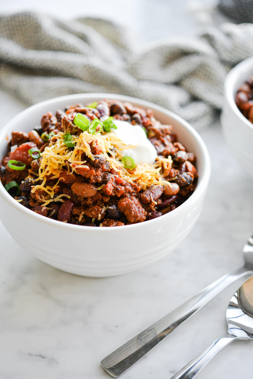 a white bowl filled with beef chili topped with sour cream, green onion, and shredded cheese sitting on a marble surface