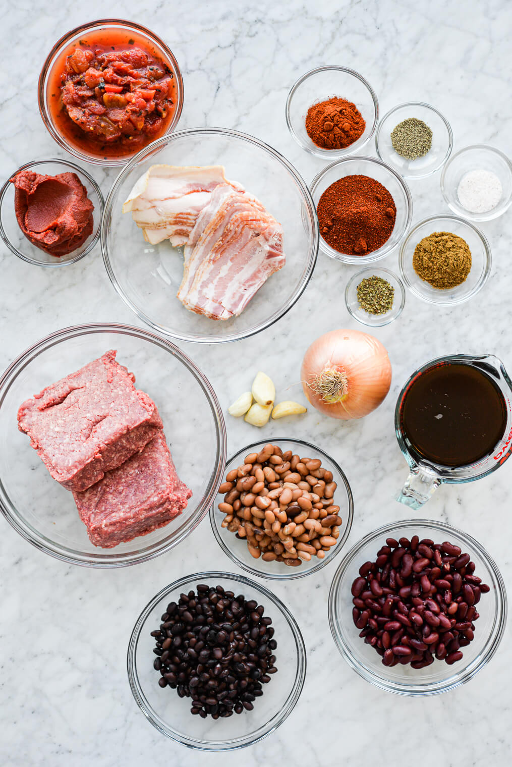 all of the ingredients for homemade beef chili (bacon, beef, tomatoes, tomato paste, beef broth, beans, onion, garlic, and spices) sitting in separate clear glass bowls on a marble surface