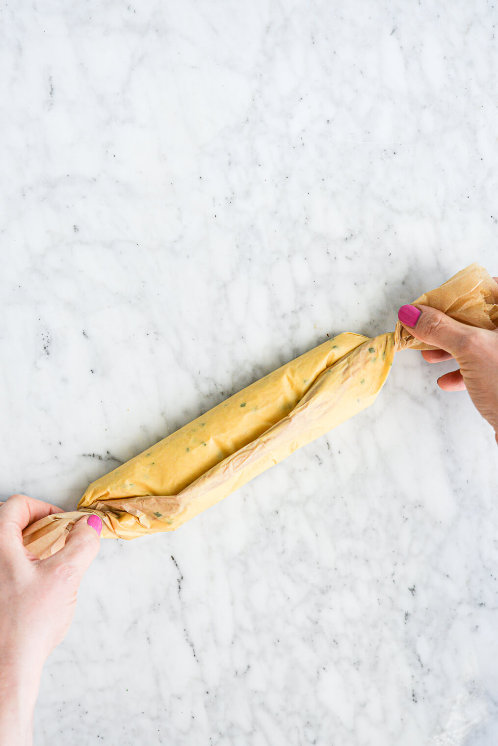 a woman's hands folding parchment paper over a log of compound garlic herb butter. All on a marble surface.
