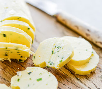 a log of compound garlic and herb butter sliced in 8 pats sitting on a wooden cutting board next to a knife