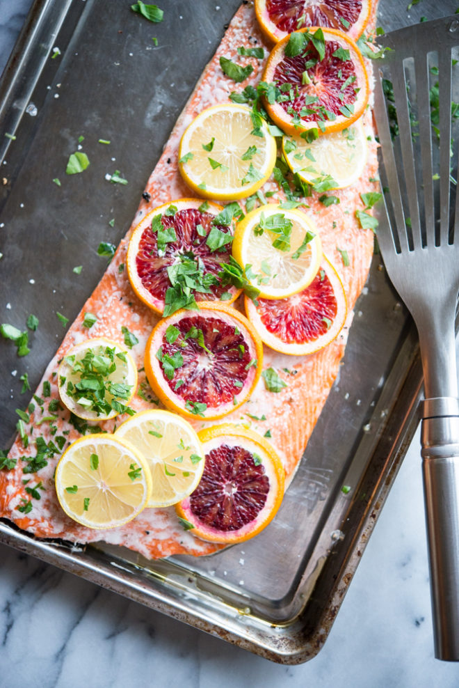 side view of a filet of citrus roasted salmon with thinly sliced blood oranges and lemons laying over top