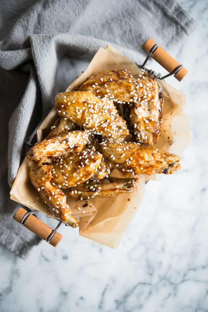 Paleo teriyaki Chicken wings in a wire basket on a marble surface