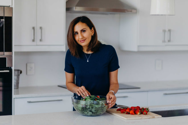 yumna jawad of feel good foodie standing at a counter behind a clear glass bowl of lettuce greens and a cutting board with whole strawberries on it
