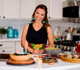 Yvette Marquez-Sharpnack from Muy Bueno standing at the kitchen counter in front of an array of authentic Mexican dishes