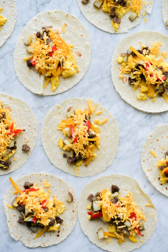 open breakfast tacos filled with scrambled eggs, potatoes, bell peppers, shredded cheese, and crumbed breakfast sausage laying on a marble surface