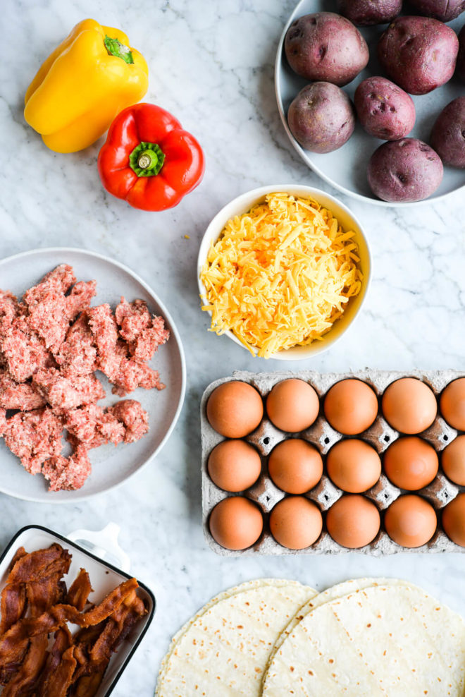 red potatoes, bell peppers, eggs, shredded cheese, uncooked breakfast sausage, bacon, and tortillas laying out on a marble surface