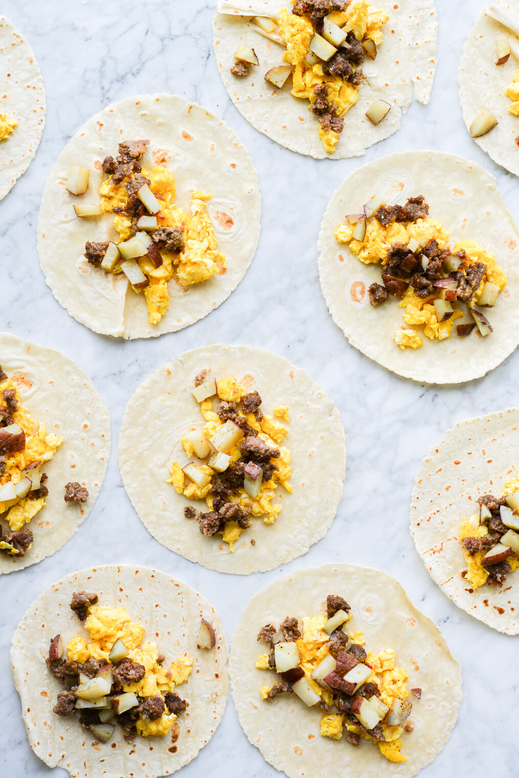 open breakfast tacos filled with scrambled eggs, potatoes, and crumbed breakfast sausage laying on a marble surface