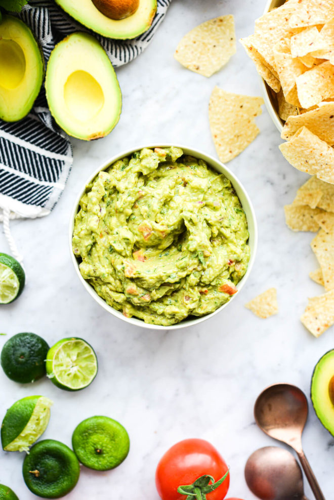 a bowl of guacamole with halved avocados, tortilla chips, tomatoes, red onions, cilantro, and lime halves sitting around it