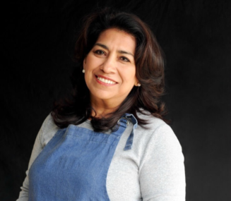 Mely Martinez of Mexico in My Kitchen standing in front of a black background with a denim apron on smiling at the camera