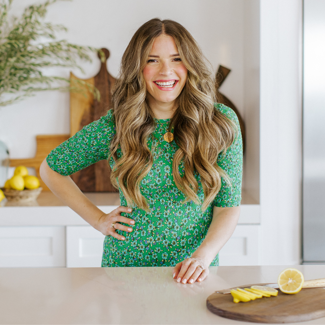 image of a woman in a green dress standing at a kitchen counter with a cutting board with sliced lemons in front of her